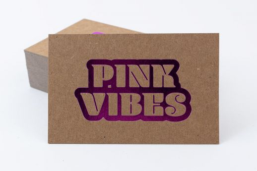 Kraft business card with metallic pink foil stamping.